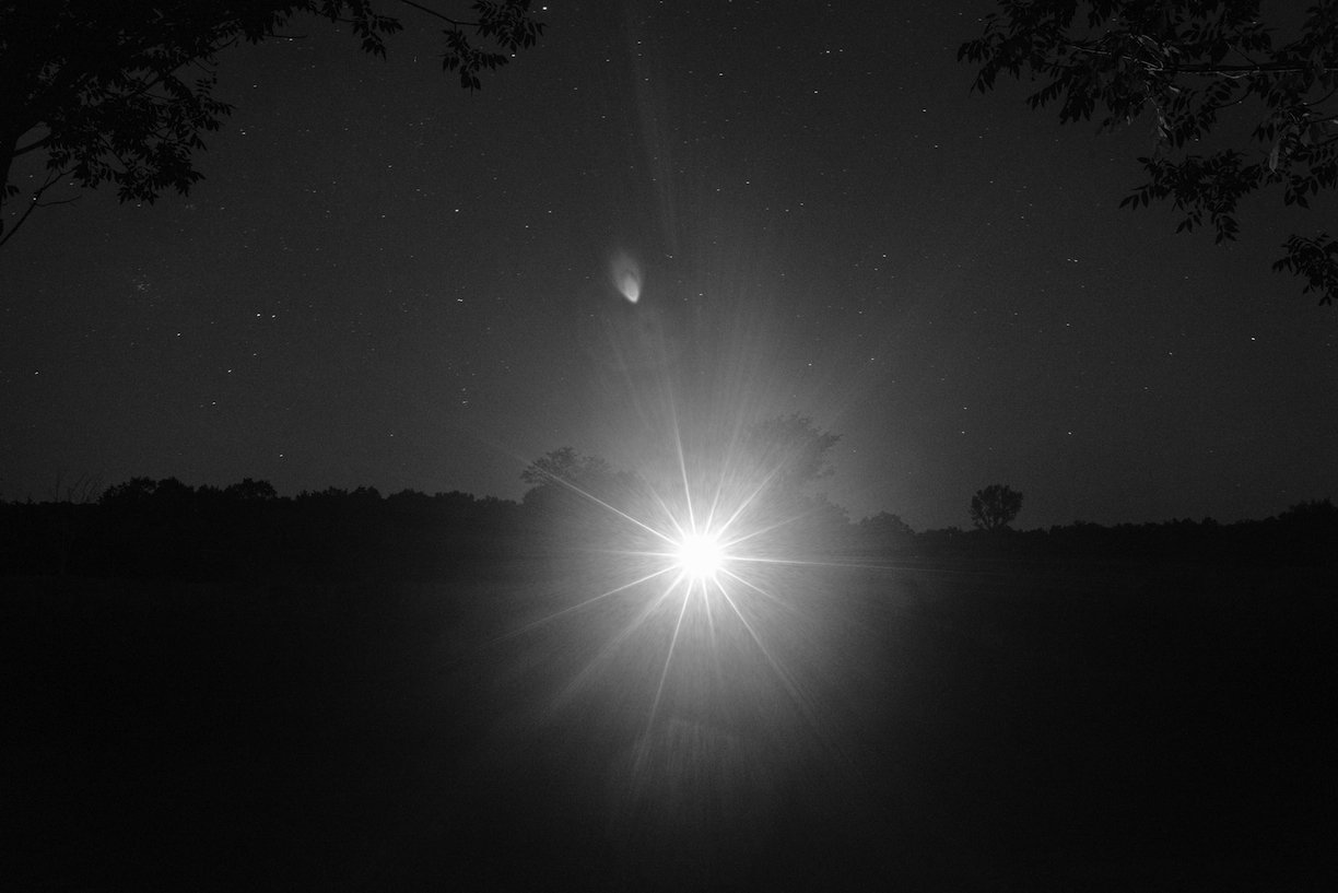 Black and white image of light flare in a dark landscape