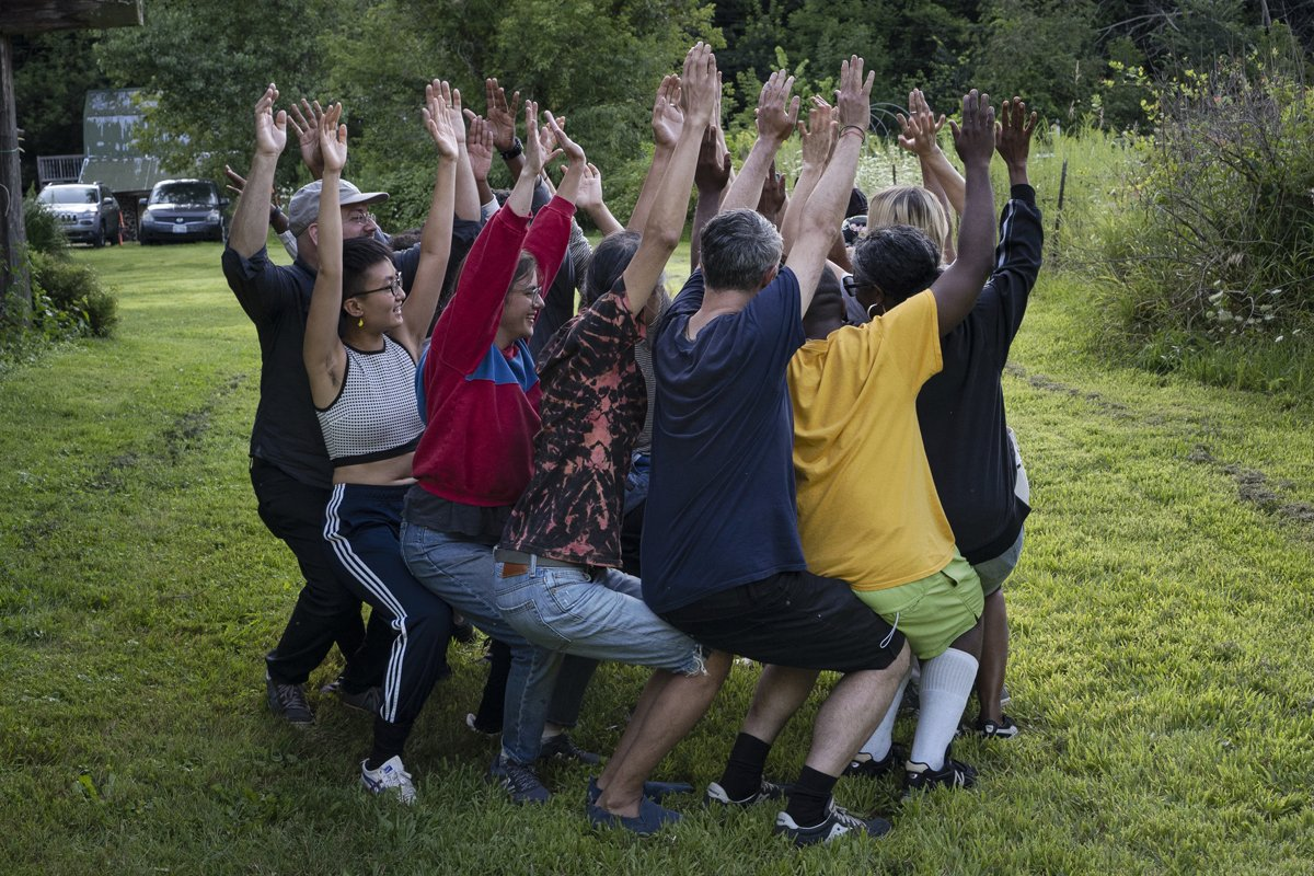 Artists participating in group exercise, arranged in circle with arms in the air