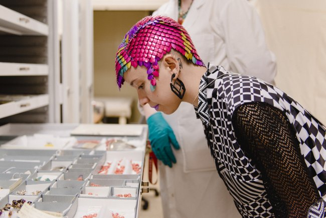 Image of person wearing colorful head dress looking down at pieces of jewelry