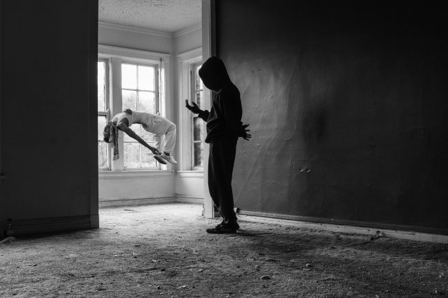 Black and white photography of two figures in a house, one is levitating on their back.