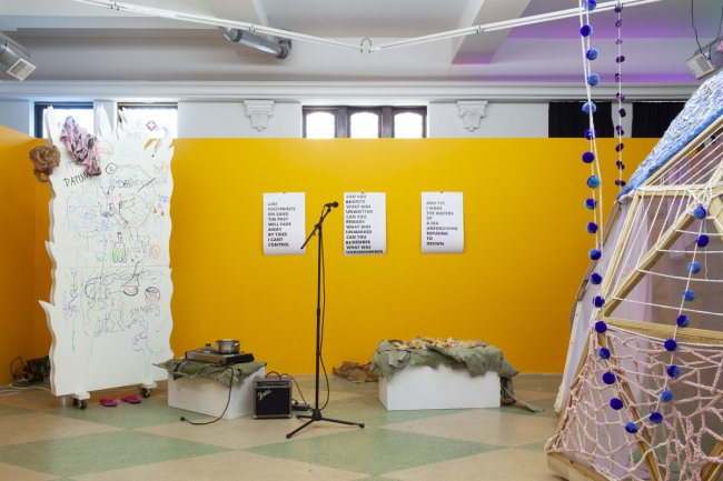 Installation image of exhibition with microphone and pa, crocheted dome, and white room divider with drawings in marker.