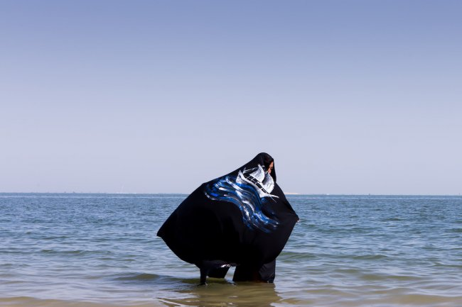 Photograph of person standing knee deep in water wearing a cloak with a ship painted on it.